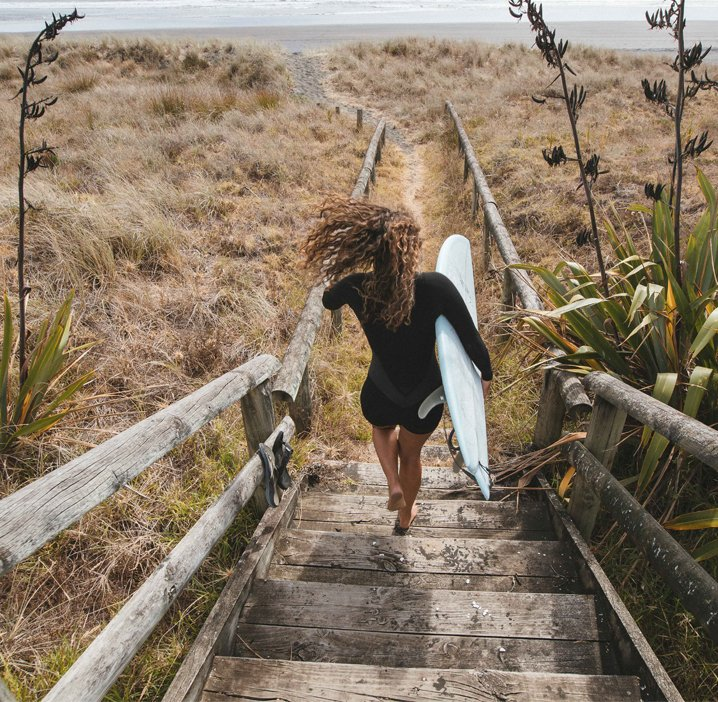 Female surfer running down stairs to beach