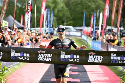 Subaru of New Zealand Brand Ambassador Braden Currie, of Wanaka, grabs the winner's tape at the finish line of the Kellogg's Nutri-Grain IRONMAN 70.3 Taupo title yesterday. PHOTO CREDIT: DARRYL CAREY