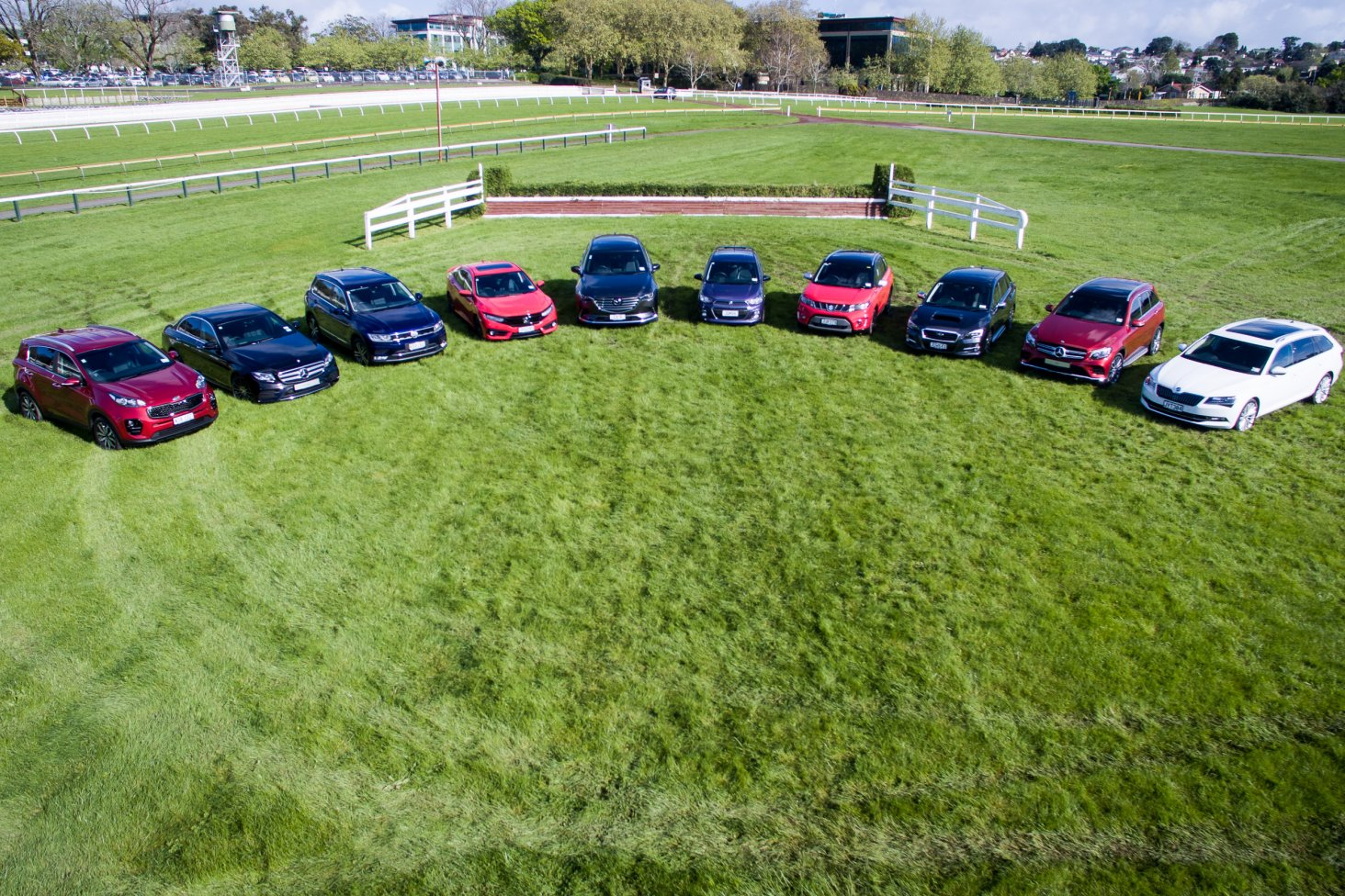 The 2016 New Zealand Car of the Year top 10 finalists take their marks on the track at Ellerslie Racecourse. From left: Kia Sportage, Mercedes-Benz E-Class, Volkswagen Tiguan, Honda Civic, Mazda CX-9, Holden Spark, Suzuki Vitara, Subaru Levorg, Mercedes-B