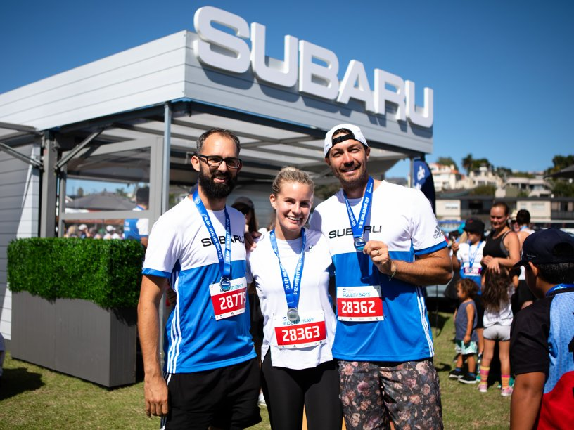 Art Green and Matilda Green with friend David at the Subaru stand for Round the Bays.
