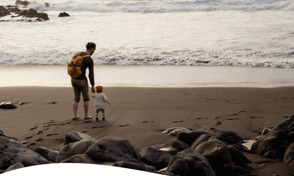 Dad with toddler on beach walking towards surf