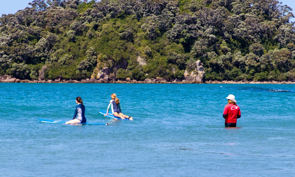 Grace and Sophie waiting for waves with the surf instructor in safe waters. PC: Surf2Surf