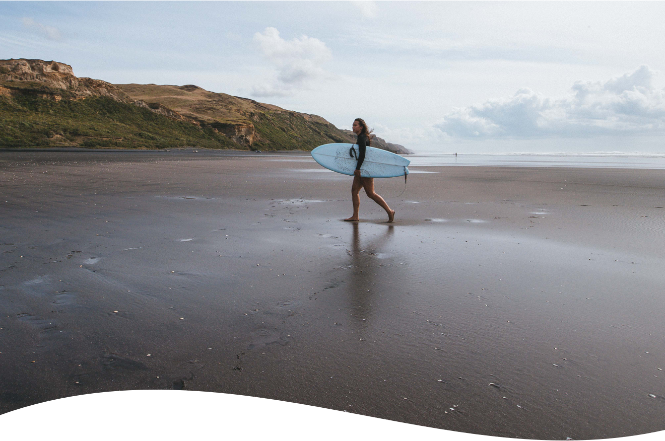 Girl on a remote beach holding a surfboard.